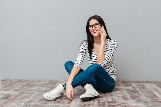 Foto de mujer joven feliz con anteojos sentado en el suelo mientras habla por teléfono sobre una superficie gris. mira a un lado.