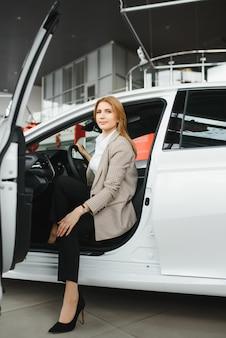 Foto de mujer joven feliz sentada dentro de su coche nuevo. concepto de alquiler de coches