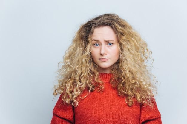 Foto de mujer joven infeliz disgustada con cabello rubio tupido rizado
