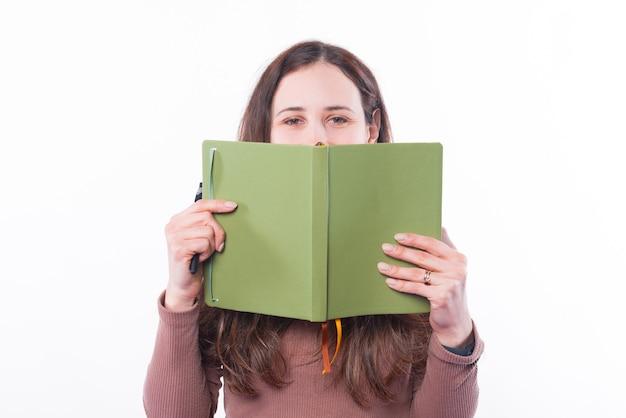 Foto de mujer joven que cubre su rostro con planificador de agenda verde