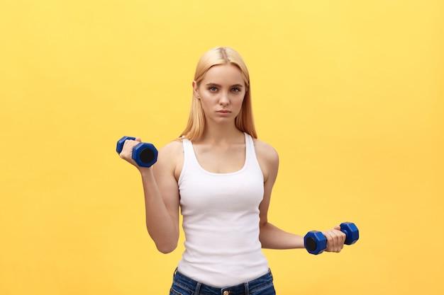 La foto de la mujer joven seria de los deportes hace ejercicios con pesas de gimnasia aisladas sobre fondo amarillo de la pared.