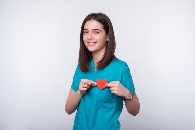 La foto de una mujer joven sonriente está vistiendo el uniforme del doctor y está sosteniendo poco corazón rojo. cuida tu salud.