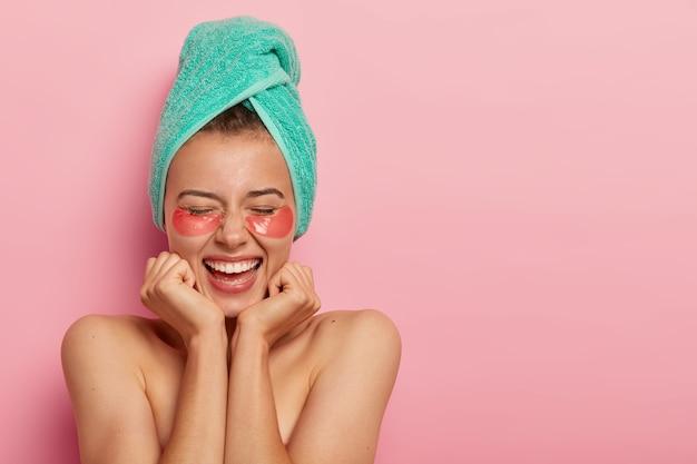 La foto de una mujer llena de alegría toca la barbilla con ambas manos, muestra los hombros desnudos, tiene una piel suave y saludable, elimina las arrugas debajo de los ojos con parches cosméticos