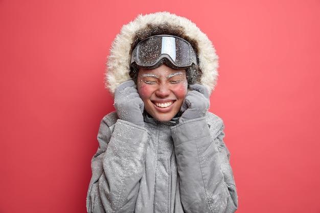 Foto de mujer llena de alegría viste capucha de chaqueta gris sonríe agradablemente tiene la cara roja cubierta de escarcha va a esquiar durante diciembre.
