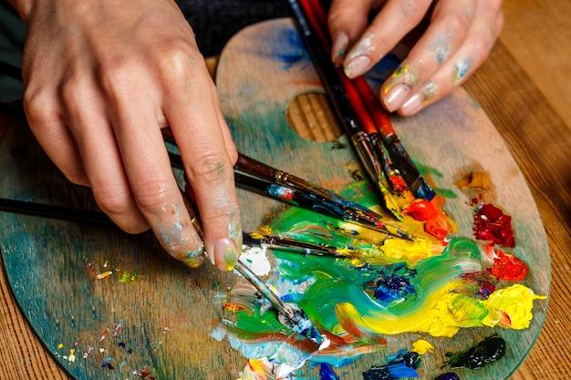 Foto de mujer mezclando pinturas al óleo sobre paleta de cerca