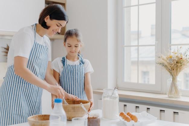 Foto de mujer morena con delantal a rayas, mezcla ingredientes con batidor, muestra a la pequeña hija cómo cocinar, se para en la cocina junto a la mesa con productos frescos. madre e hijo ocupados preparando comida
