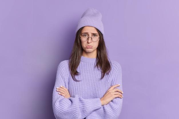 Foto de mujer morena disgustada que mira con expresión ofendida mantiene las manos cruzadas siendo lastimado por alguien que usa gafas redondas de ropa púrpura la mujer gruñona tiene mal humor. concepto de resentimiento