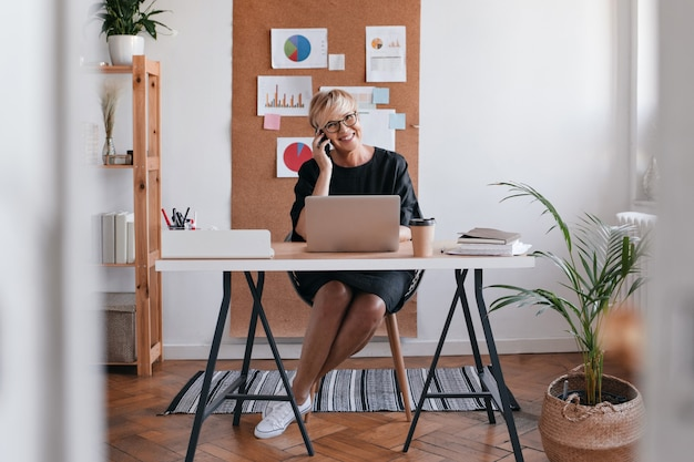 Foto de mujer de negocios en vestido negro hablando por teléfono