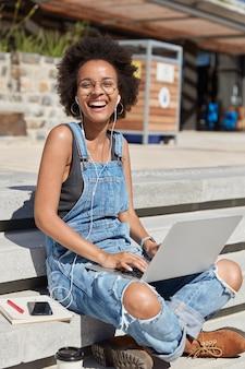 Foto de una mujer negra alegre que viste un mono de mezclilla de moda, zapatillas, lauhgs felizmente, escucha música agradable, busca un lugar interesante para hacer excursiones en una computadora portátil, utiliza tecnologías modernas