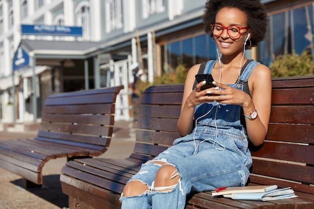 Foto de mujer negra alegre sostiene celular, escribe mensajes de texto, usa audífonos, escucha música, vestida con overoles andrajosos, modela al aire libre, disfruta de la lista de reproducción. tecnologías modernas, comunicación online
