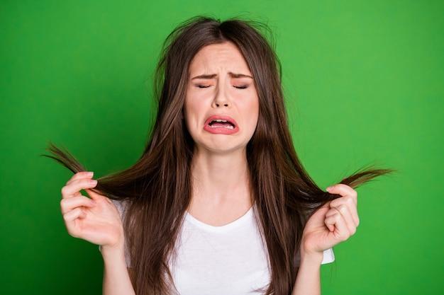 Foto de mujer ofendida llorando usar camiseta blanca sosteniendo los brazos del cabello extremos secos fondo de color verde aislado
