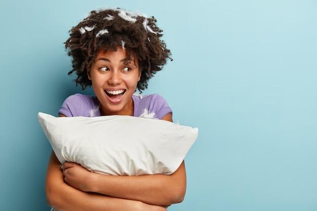 Foto de mujer optimista de piel oscura con cabello rizado, abraza una almohada suave, tiene buen humor después del sueño de la tarde, posa con plumas en la cabeza, posa sobre una pared azul, espacio en blanco para información