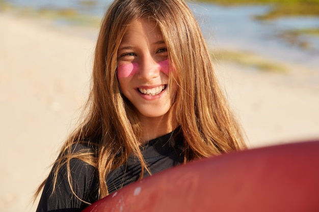 Foto de mujer de pelo claro complacida con una gran sonrisa, tiene zinc de surf en la cara para protegerse del sol, feliz después de un viaje de surf con un amigo