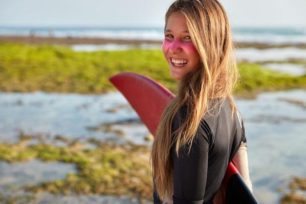Foto de mujer de pelo largo satisfecha sostiene la tabla de surf bajo la mano, se ve positivamente