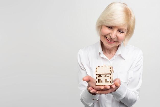 Una foto de una mujer que tiene una pequeña casa de juguete en la mano. ella es vieja y quiere tener algunas garantías por el resto de su vida.
