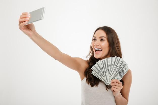 Foto de una mujer rica y afortunada haciendo selfie en un teléfono móvil plateado mientras sostiene un montón de billetes de dólares, aislado sobre la pared blanca