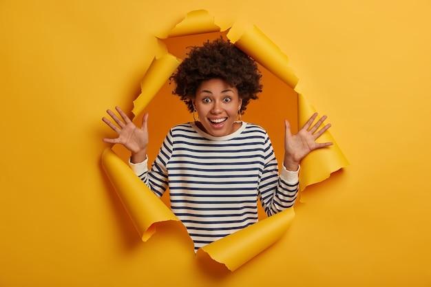 Foto de mujer rizada alegre levanta las palmas, se regocija en la reunión final con un amigo cercano, vestida con un jersey casual a rayas, gestos de felicidad, posa en un fondo de papel rasgado