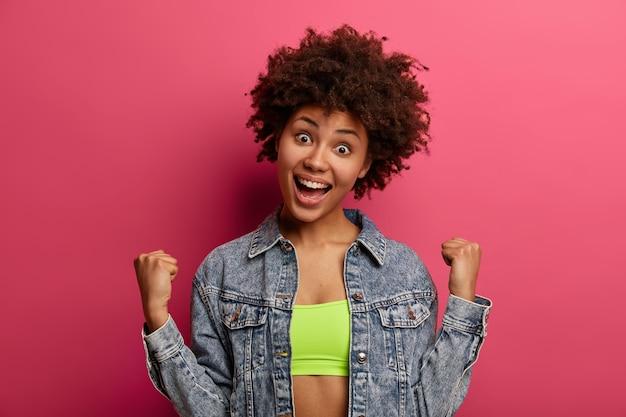 Foto de mujer rizada llena de alegría aprieta los puños, se erige como ganador