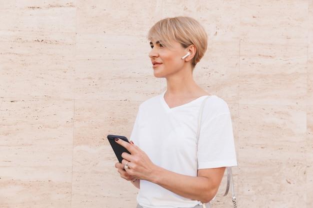 Foto de una mujer rubia europea con camiseta blanca que usa el teléfono móvil para escuchar música, mientras está de pie contra la pared beige al aire libre con auricular bluetooth