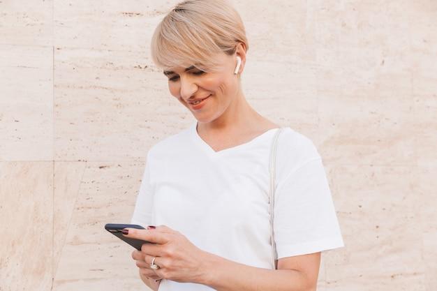 Foto de mujer rubia feliz con camiseta blanca mediante teléfono móvil, mientras está de pie contra la pared beige al aire libre con auriculares bluetooth