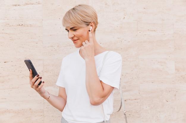 Foto de mujer rubia feliz con camiseta blanca con teléfono móvil, mientras está de pie contra la pared beige al aire libre y tocando el auricular bluetooth