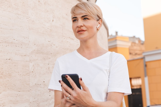 Foto de mujer rubia feliz vistiendo camiseta blanca y auricular bluetooth mediante teléfono móvil, mientras camina por las calles de la ciudad