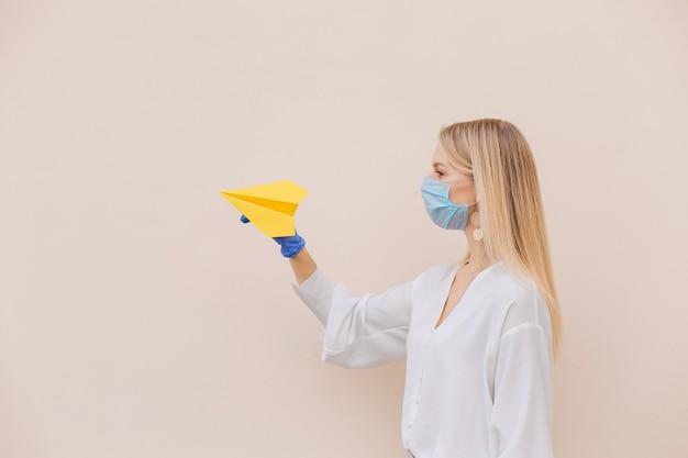 Foto de mujer rubia positiva en una máscara médica y guantes protectores de látex azul