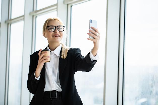 Foto de mujer secretaria en ropa formal de pie sosteniendo café para llevar en la mano y tomando selfie en teléfono móvil en la oficina