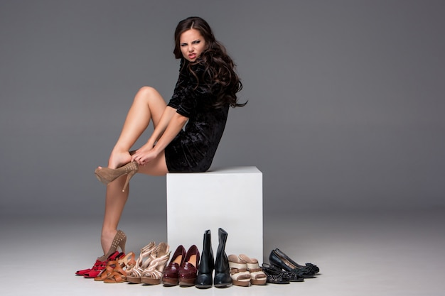 Foto de mujer sentada probándose zapatos de tacón alto