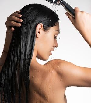 Foto de una mujer sexy en la ducha lavándose el cabello largo