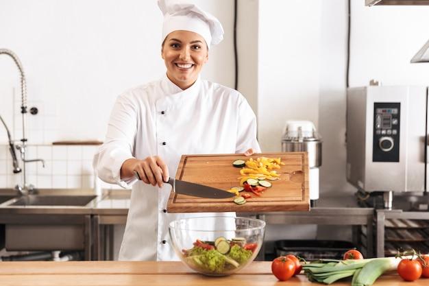 Foto de mujer sonriente chef vistiendo uniforme blanco haciendo ensalada con verduras frescas, en la cocina del restaurante