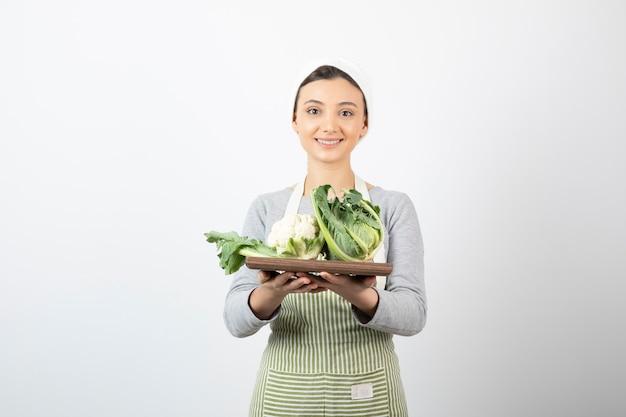 Foto de una mujer sonriente en delantal sosteniendo una placa de madera con coliflores