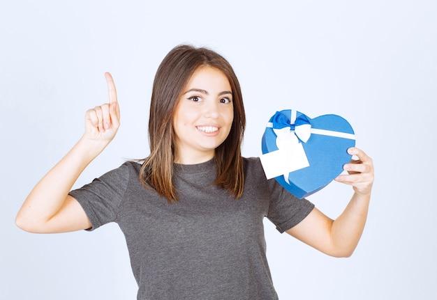 Foto de mujer sonriente joven apuntando con un dedo hacia arriba y sosteniendo una caja de regalo en forma de corazón.