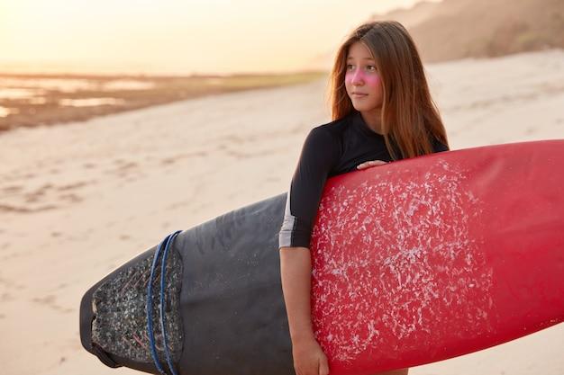 Foto de mujer surfista en traje de baño negro, tiene tabla de surf, ha paseado por el mar o el océano