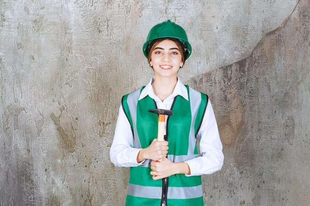 Foto de mujer trabajadora de la construcción en casco verde sosteniendo un martillo