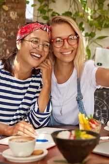 Foto de mujeres alegres de raza mixta cooperan juntas, hacen una foto selfie para compartir en las redes sociales