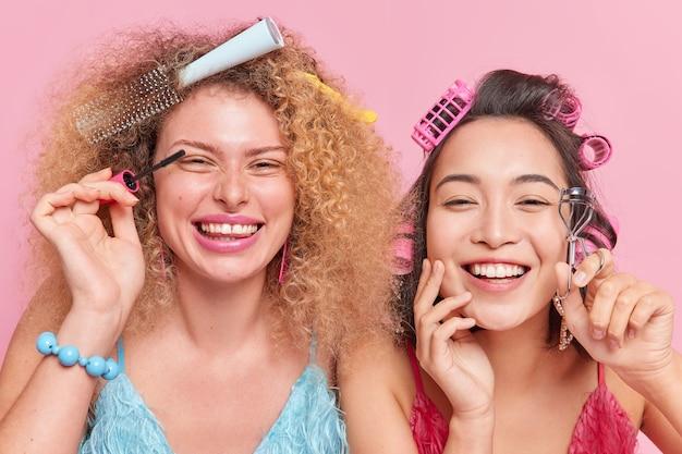 Foto de mujeres de raza mixta felices que hacen a diario maquillarse aplicar rímel usar pestañas rizador sonrisa ampliamente prepararse para fecha o fiesta aislada sobre fondo rosa de estudio. belleza y concepto femenino.