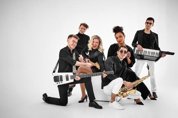 Foto, de, multiétnico, música, banda, en, studio., músicos, y, mujer, solista, posar, encima, blanco