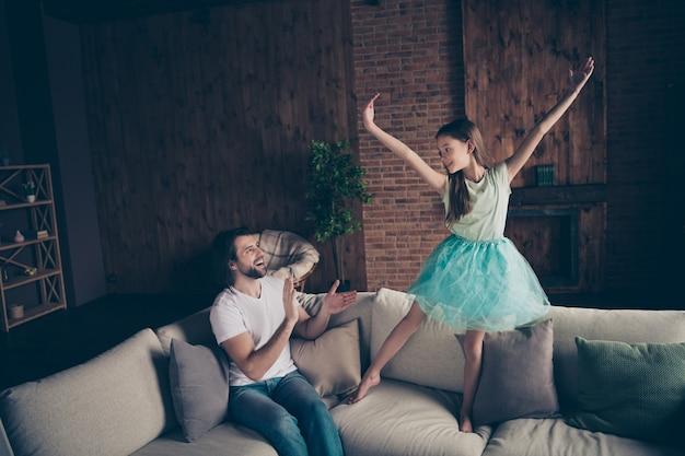 Foto de niña bonita enérgica emocionado guapo papá viendo hija escuela baile rendimiento sentado sofá aplaudiendo brazos ovación casa habitación interior