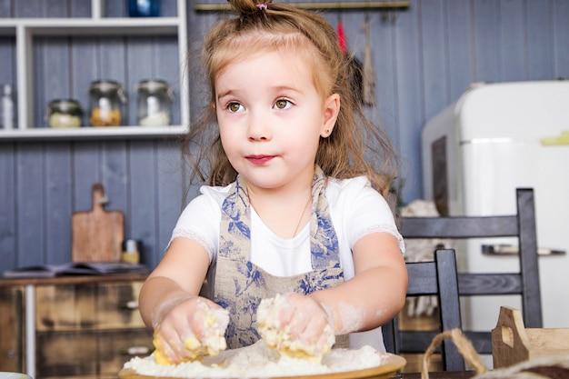Foto de niña cocina en la cocina ella misma