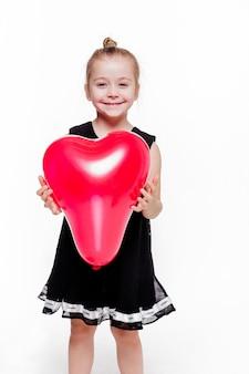 Foto de niña con un elegante vestido negro sosteniendo un globo rojo en forma de corazón