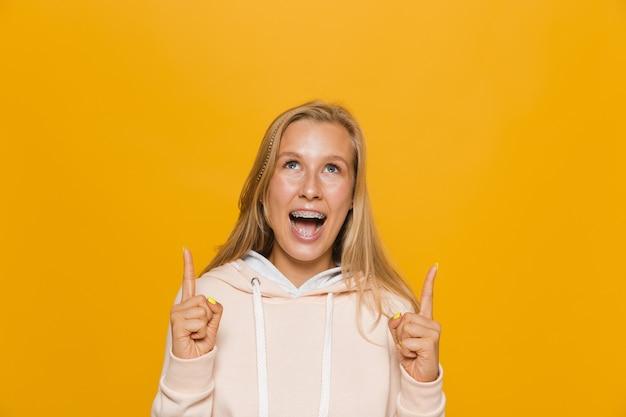 Foto de niña de la escuela emocionada con aparatos dentales apuntando con el dedo hacia arriba en el copyspace, aislado sobre fondo amarillo