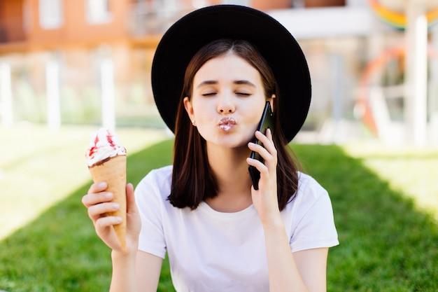 Foto de una niña, hablando por teléfono celular, sosteniendo un helado con una camiseta blanca y un sombrero en la calle