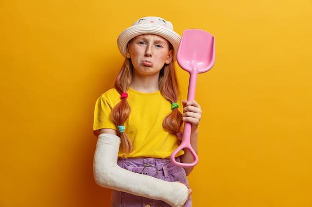 Foto de niña pelirroja disgustada con pecas, frunciendo los labios y se ve triste, no puede jugar con amigos, sostiene una pala de juguete, tiene un brazo roto en yeso, usa sombrero, camiseta y falda