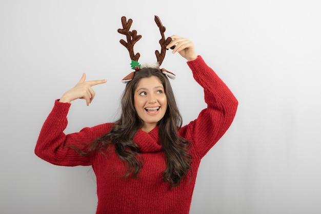 Foto de niña positiva señalar con el dedo a la venda de ciervo navidad.