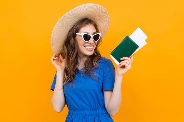 Foto de una niña turista con un boleto y un pasaporte en sus manos contra el fondo de una pared naranja