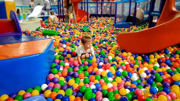 Foto de niño jugando en la piscina llena de bolas de plástico colroful. niño divirtiéndose en el patio de recreo en el centro comercial
