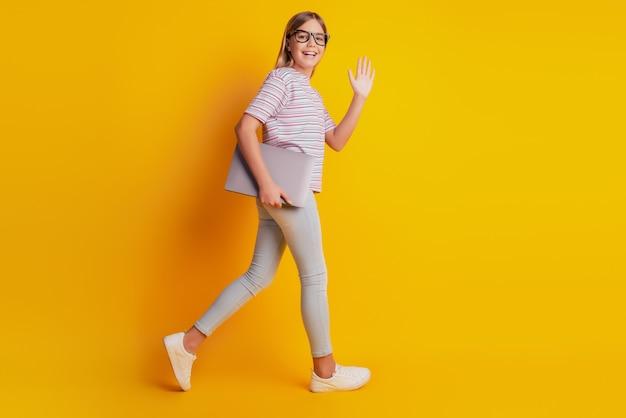 Foto de niño niña vaya mantenga la mano de onda portátil aislada sobre fondo amarillo