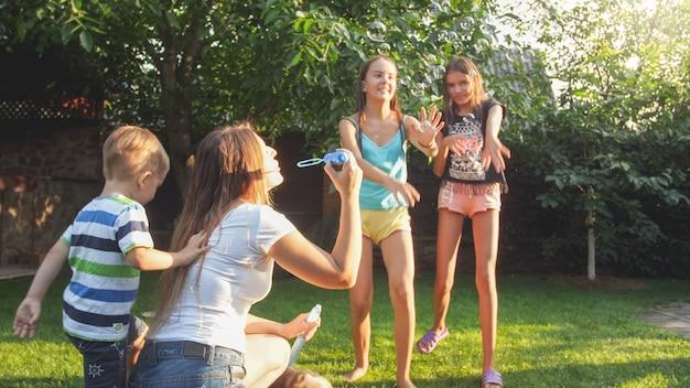 Foto de niños riendo felices que soplan y catan pompas de jabón en el patio de la casa. familia jugando y divirtiéndose al aire libre en verano