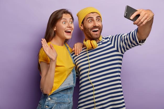 Foto de la novia y el novio llenos de alegría toman un retrato selfie en un teléfono inteligente, hacen videollamadas, saludan a la cámara, tienen expresiones alegres, se divierten juntos, posan en interiores contra el fondo púrpura